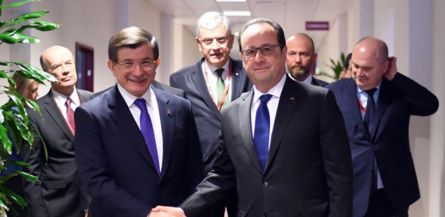 French President Francois Hollande (center right) shakes hands with Turkish Prime Minister Ahmet Davutoglu, (center left) prior to a meeting during an EU summit in Brussels on Friday.
