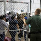 In this photo provided by U.S. Customs and Border Protection, a U.S. Border Patrol agent watches as people who've been taken into custody related to cases of illegal entry into the United States, stand in line at a facility in McAllen, Texas, Sunday, June 17, 2018.