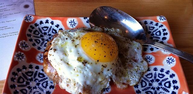 Autre Monde Cafe crepinette, wilted greens, and griddled egg