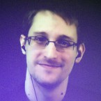"Edward Snowden, who is in Moscow, is seen on a giant screen during a live video conference for an interview as part of an Amnesty International event in Paris in December 2014. The House Permanent Select Committee on Intelligence published a summary report accusing Snowden of causing ""tremendous damage to U.S. national security."""