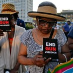 Denise Tucker, right, and Imani Parker bow their heads during a moment of silence while attending the End Gun Violence Candlelight Vigil in recognition of Gun Violence Awareness Month, Wednesday, June 1, 2016, in New York.
