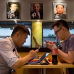 Customers look at his mobile devices near the Funiutang beef noodle restaurant displaying portraits of former Communist leaders including Karl Marx and Mao Zedong to promote their food in Beijing on Sunday, July 3, 2016. In a televised speech on the 95th anniversary of the party's formation on July 1, 2016, Chinese president Xi Jinping has urged the 88-million-strong Communist Party to embrace its Marxist roots as he delivered an emphatic call for ideological discipline and a vigorous defense of party rule.