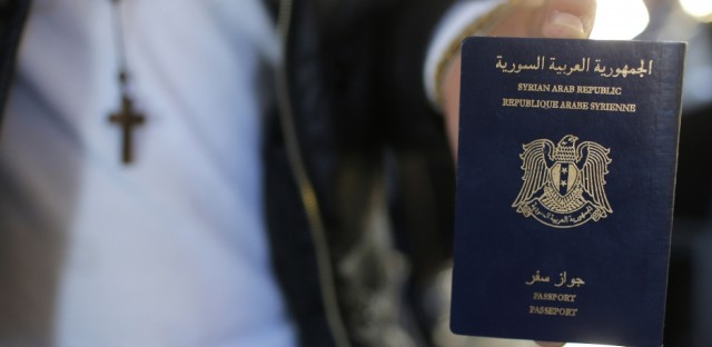 Syrian refugee Ghassan Aleid displays his Syrian passport at a terminal at the Charles-de-Gaulle Airport in Roissy, France.