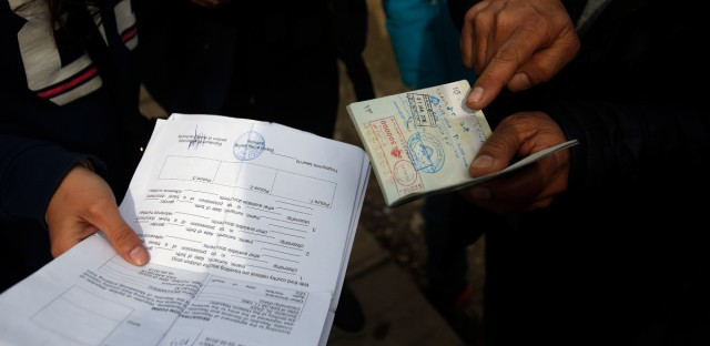 Migrants showing registration papers and Syrian passports in the transit center for refugees in Sid, about 100 km west from Belgrade, Serbia, Thursday, March 3, 2016. Greece's prime minister Alexis Tsipras has called for sanctions to be imposed on European Union states that refuse to take in their share of the hundreds of thousands of refugees flowing into the continent through his country.