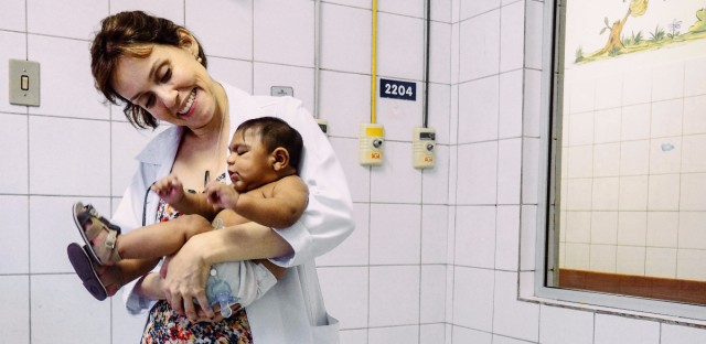 Dr. Regina Coeli holds 4-month-old Enzo Thamires in an examination room of the Oswaldo Cruz public hospital in the Brazilian city of Recife. Catherine Osborn/for NPR