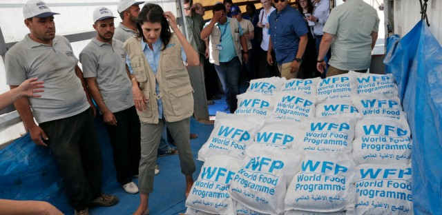 U.S. Ambassador to the U.N. Nikki Haley, center left, walks past food parcels provided by the World Food Programme, part of the humanitarian aid shipments into Syria, during a visit at the Reyhanli border crossing with Syria, near Hatay, southern Turkey, Wednesday, May 24, 2017. (AP Photo/Burhan Ozbilici, Pool)