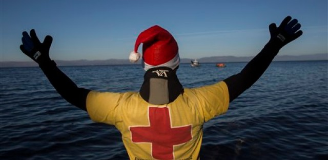 A member of the Greek Red Cross wearing a Santa Claus hat calls the attention of refugees and migrants approaching the Greek island of lesbos, on Thursday, Dec. 24, 2015. The Geneva-based International Organization for Migrants says more than 1 million people have entered Europe as of Monday. Almost all came by sea, while 3,692 drowned in the attempt.