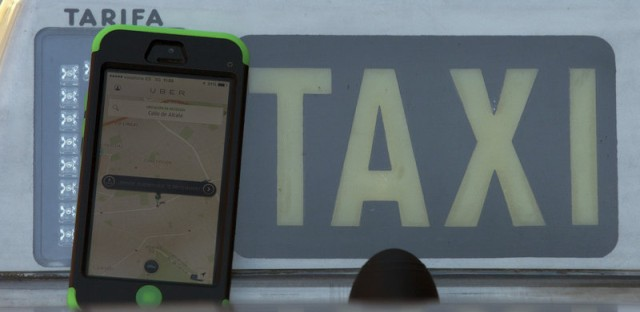The Uber smartphone app is seen next to a taxi sign.