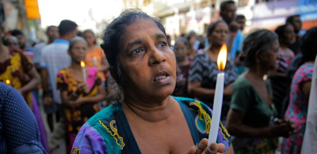 Sri Lankans pray during a three minute nationwide silence observed to pay homage to the victims of Easter Sunday's blasts outside St. Anthony's Shrine in Colombo, Sri Lanka, Tuesday, April 23, 2019. A state of emergency has taken effect giving the Sri Lankan military war-time powers not used since civil war ended in 2009. Police arrested 40 suspects, including the driver of a van allegedly used by suicide bombers involved in deadly Easter bombings.
