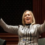"Illinois Rep. Katherine Cloonen, D-Kankakee, acknowledges applauds after singing ""God Bless America"" while on the House floor during veto session at the Illinois State Capitol Thursday, Dec. 1, 2016, in Springfield, Ill. (AP Photo/Seth Perlman)"