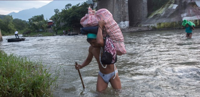 Men carry loads of supplies as they cross the Suchiate river from Guatemala into Talisman, Mexico, Friday, June 21, 2019. Mexico's foreign minister says that the country has completed its deployment of some 6,000 National Guard members to help control the flow of Central American migrants headed toward the U.S