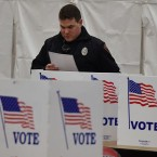 A police officer votes at Belmont High School on Feb. 9, 2016, in Belmont, N.H., during the New Hampshire presidential primary. The state's lawmakers are now debating bills that would tighten residency requirements for new voters.