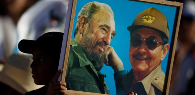 A girl holds up a photo of Cuba's revolutionary leader Fidel Castro and his brother, President Raul Castro, at the May Day celebration in Revolution Square in Havana, Cuba in 2011.