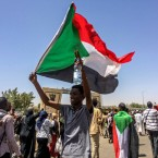 Protesters carry national flags at at rally in front of the military headquarters in the capital Khartoum, Sudan, Monday, April 8, 2019. Organizers behind anti-government demonstrations in Sudan said security forces attempted to break up a sit-in outside the military headquarters. A spokeswoman for the Sudanese Professionals Association told The Associated Press that clashes erupted early Monday between security forces and protesters, who have been camped out in front of the complex in Khartoum since Saturday.