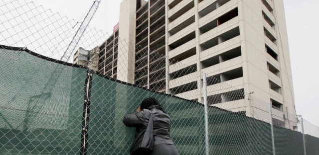 Neighborhood resident Deidre Brewster peers through a fence as demolition begins at the last high-rise at Chicago's Cabrini-Green public housing complex, Wednesday, March 30, 2011, in Chicago. Cabrini-Green was built on Chicago's North Side starting in the 1940s.