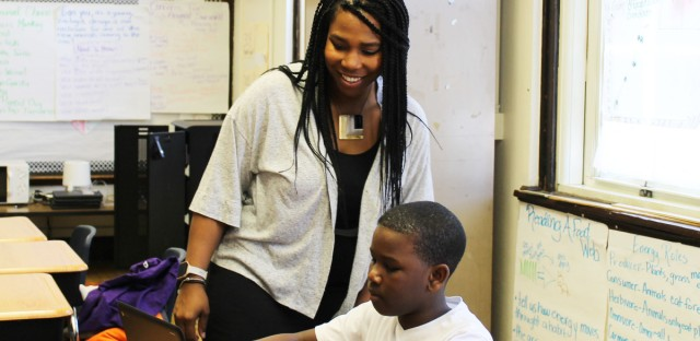 Burke Elementary School teacher Jakil Hill Turner helps a student in her fifth-grade class. Turner discovered Burke through a Chicago Public Schools program that helps place quality teacher candidates in high-need schools. (Arionne Nettles/WBEZ)