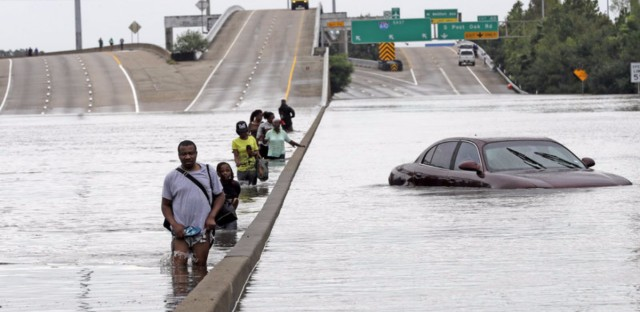 Residents of southeast Texas are taking stock and trying to absorb record flooding brought by Hurricane Harvey. Here, evacuees wade down a flooded section of Interstate 610 in Houston as floodwaters continued to rise Sunday.