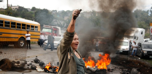 An anti-government protestor chants slogans against Honduras President Juan Orlando Hernandez as protesters block a road on the outskirts of Tegucigalpa, Honduras, Thursday, Dec. 7, 2017.