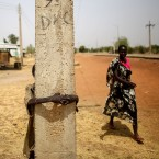 The town of Bentiu, in South Sudan, has been nearly abandoned. On the main road, a boy hides behind a telephone pole.