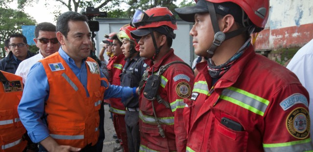 "Guatemalan President Jimmy Morales greets rescue workers during his visit to a site near the Volcan de Fuego, or ""Volcano of Fire,"" in Escuintla, Guatemala, Wednesday, June 6, 2018."