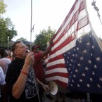 Father Pfleger of St. Sabina Church hangs the American flag upside down outside his church Aug. 31 as demonstrators protest the recent uptick in homicides across Chicago. Thirteen people were fatally shot over the weekend, bringing the city's annual toll to at least 500 murders.