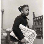 Portrait of a young African American boy selling the Chicago Defender on a street corner on Chicago's South Side, April 1942. The boy carries a full bag of the daily newspaper and holds one in his hand to flog.