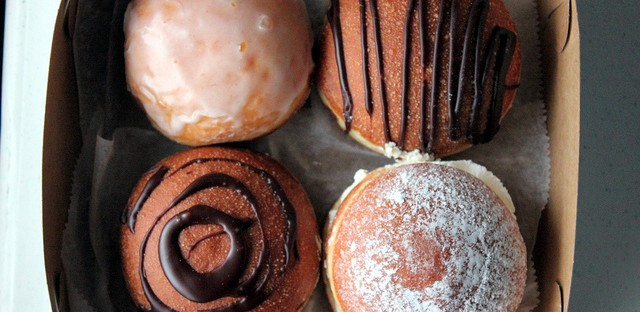 Box of rose hip, drunken chocolate, strawberry whipped cream, and chocolate raspberry jam paczki from Delightful Pastries in Chicago