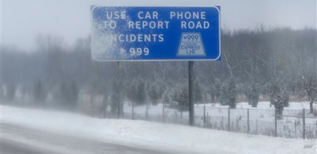 A sign is covered by snow on South bound of I-294 in Des Plaines, Ill., Saturday, Feb. 1, 2014.