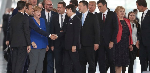 French President Emmanuel Macron, second left, shakes hands with Italian Prime Minister Giuseppe Conte, center, as they stand with other heads of state during a summit of NATO heads of state and government at NATO headquarters in Brussels, Wednesday, July 11, 2018.