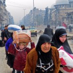 Syrian residents, fleeing violence in the Bustan al-Qasr neighborhood, arrive in Aleppo's Fardos neighborhood on Tuesday after government troops retook the area from rebel fighters.