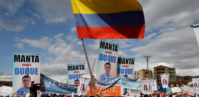 A supporters of Ivan Duque, presidential candidate for Democratic Center party, waves a Colombian flag during a campaign rally in Soacha, in the outskirts of Bogota, Colombia, Saturday, May 12, 2018.