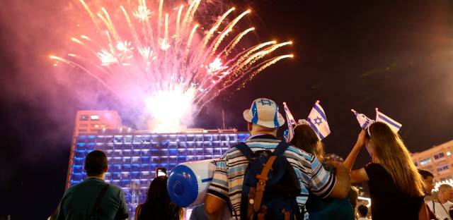 Israelis look at a fireworks set to begin the celebrations for Israel's 70th Independence Day, at Rabin square in Tel Aviv, Israel, Wednesday, April 18, 2018.