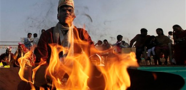 An Indian groom sits behind a flame during a ritual at a Hindu wedding ceremony outside of Mumbai.