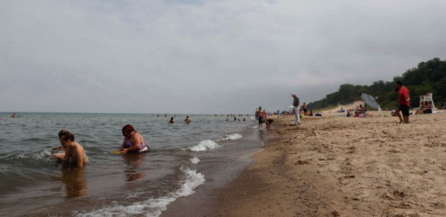 In this Aug. 10, 2015, photo, visitors relax at the beach front in Chesterton, Ind. In February, the Indiana Dunes became a national park.
