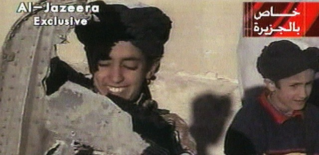 In this image made from video broadcast by the Qatari-based satellite television station Al Jazeera in 2001, a young boy, left, identified as Hamza bin Laden holds what the Taliban says is a piece of U.S. helicopter wreckage in Ghazni, Afghanistan.