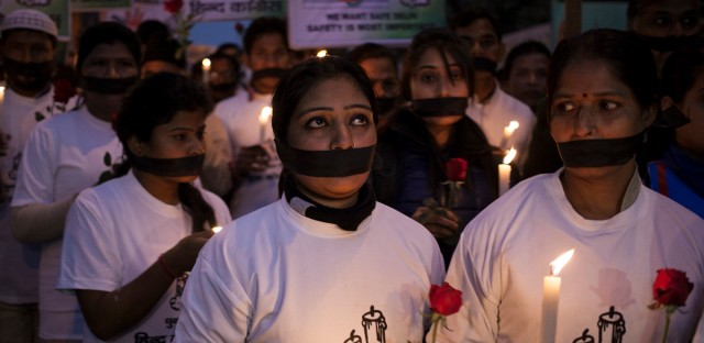 Indian women participate in a candle light vigil at a bus stop where Jyoti Singh had boarded the bus in 2012 in New Delhi.