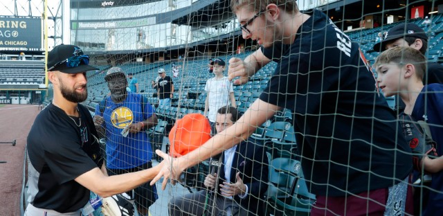 Geoffrey Boston, from Elgin, right, reaches through the newly extended netting at Guaranteed Rate Field after Miami Marlins relief pitcher Nick Anderson, left, autographed a cap before Monday night's game between the Marlins and the Chicago White Sox.