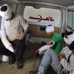 Wounded rebel fighters sit in the back of an ambulance in Aleppo on Thursday. The Syrian government and its Russian allies declared a pause in the fighting and urged rebels to leave the eastern part of the city, but clashes broke out Thursday.