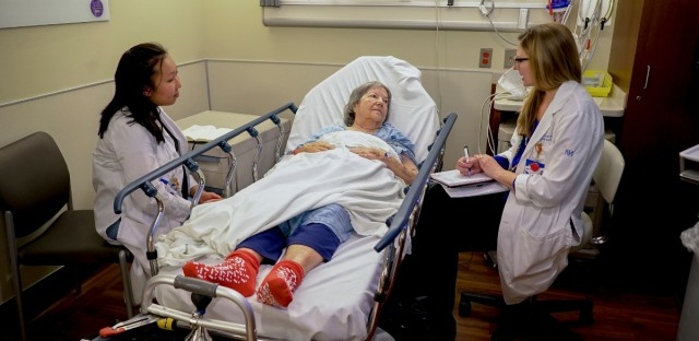 Nurses Lisa Lui-Popelka, left, and Emily Ruben, right, talk with Northwestern Memorial Hospital patient Carol Wittwer at her bedside in a special wing of the Emergency Department in Chicago on Jan. 10.
