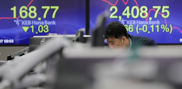 A man watches computer monitors near the screens showing the Korea Composite Stock Price Index (KOSPI), right, and the foreign exchange rate at the foreign exchange dealing room in Seoul, South Korea, Wednesday, March 7, 2018.