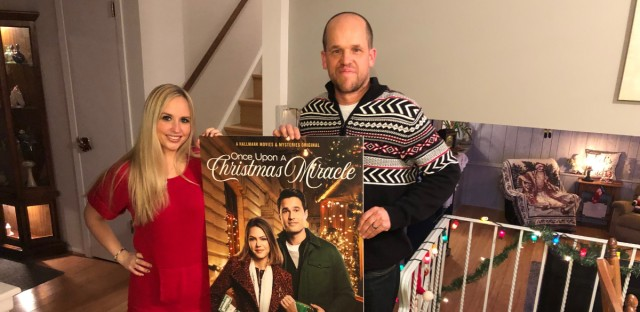 Heather Krueger and Chris Dempsey pose with a poster for the Hallmark movie based on their story