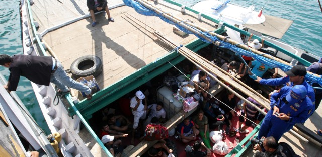 Iranian asylum seekers who were caught in Indonesian waters while sailing to Australia, sit on a boat, at Benoa port in Bali, Indonesia. Australia refuses to accept any refugees who attempt to reach its shores by boat, and pays Nauru and Papua New Guinea, which has a detention center on Manus Island, to hold them instead.