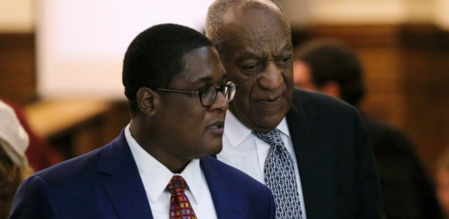 Actor and comedian Bill Cosby (right) walks with spokesperson Andrew Wyatt during deliberations in Cosby's sexual assault trial earlier this month at the Montgomery County Courthouse in Norristown, Pa.