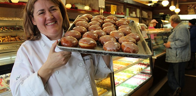 Pastry chef/owner Dobra Bielinski holds tray of plum and rose hip jam paczki at Delightful Pastries in Jefferson Park, Chicago