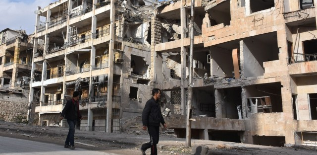 Syrians walk past destroyed buildings in the former rebel-held Ansari district in Aleppo last Friday after Syrian government forces regained control of the divided city.