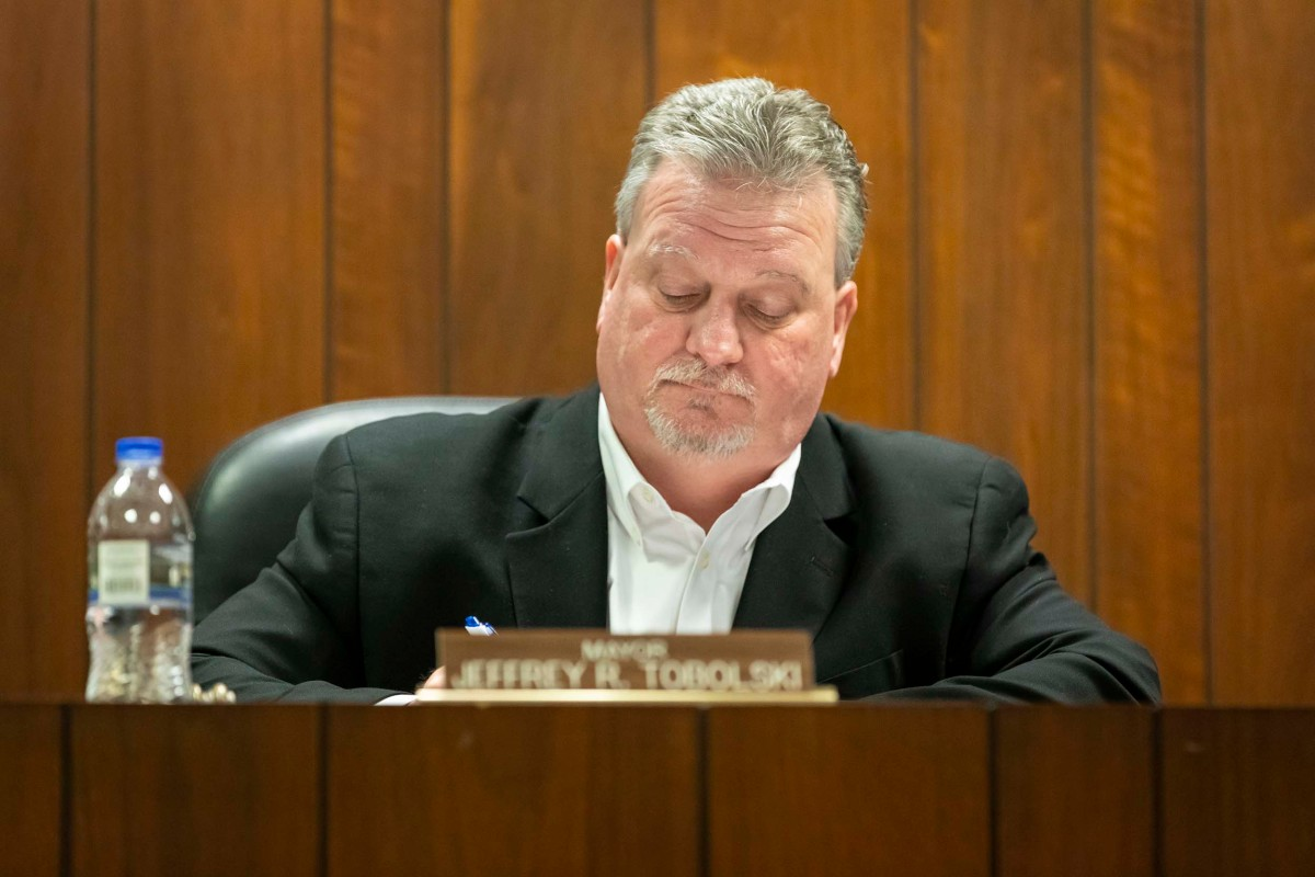 Jeff Tobolski sits in a wood-paneled room. A sign in front of him reads 'Mayor Jeffrey R. Tobolski'.