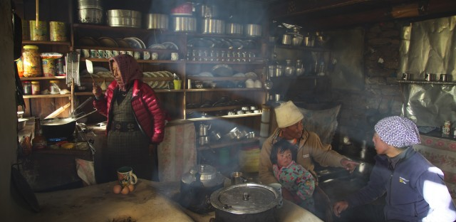 A family in Nepal prepares a meal. The use of organic fuels like wood or animal dung for cooking contributes to indoor air pollution.
