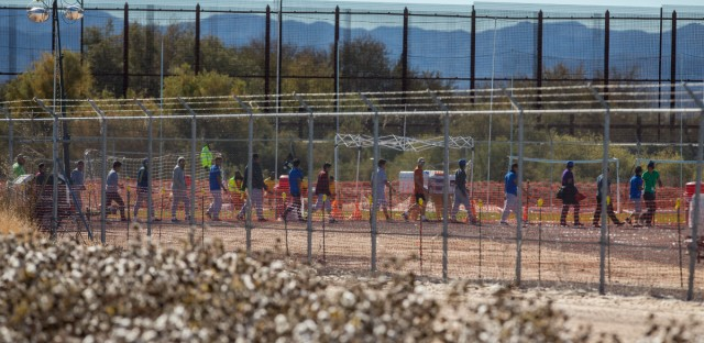 In this Nov. 15, 2018 photo provided by Ivan Pierre Aguirre, migrant teens are led in a line inside the Tornillo detention camp holding more than 2,300 migrant teens in Tornillo, Texas. The Trump administration announced in June 2018 that it would open the temporary shelter for up to 360 migrant children in this isolated corner of the Texas desert. Less than six months later, the facility has expanded into a detention camp holding thousands of teenagers - and it shows every sign of becoming more permanent.