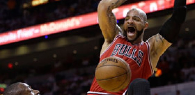 Chicago Bulls forward Carlos Boozer dunks the ball against Miami Heat guard Dwyane Wade in Game 1 of the Eastern Conference Semifinals. The Bulls lead the series 1-0.