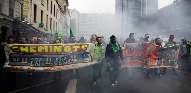 Labor union members and other people attend a demonstration against the French government and labor law reforms in Paris, Thursday, June 2, 2016. Workers are on strike at nearly all of France's nuclear plants and on the national rail service as part of months of protests over changes to labor protections. The signs read 'Railway workers from St Lazare station on strike!'.